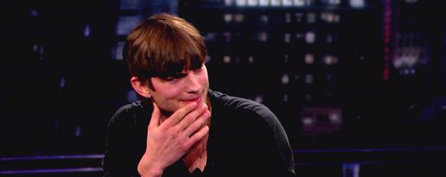 Ashton Kutcher hält seine Hand an seinen Mund