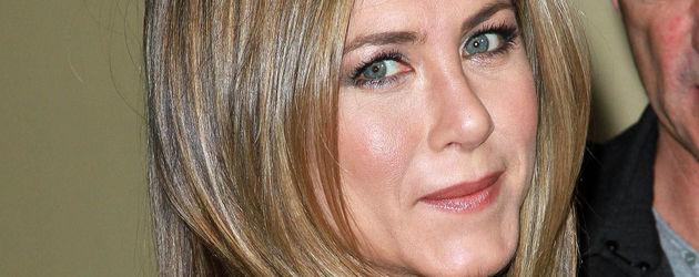 Jennifer Aniston blickt über die Schulter und freut sich