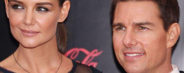 Katie Holmes guckt sketpisch, während Tom Cruise lacht