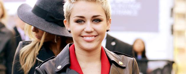 Miley Cyrus mit Lederjacke und rotem Jumpsuit