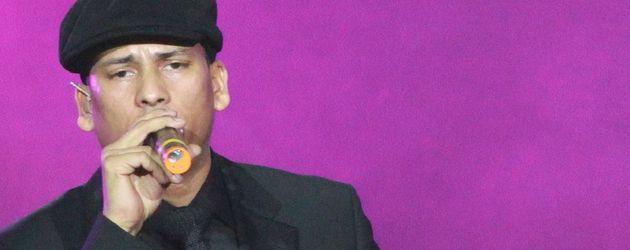 Xavier Naidoo mit Anzug, Schiebermütze und Mikrofon