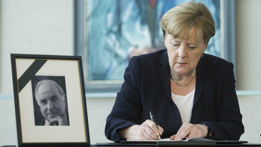 Angela Merkel mit einem Bild von Helmut Kohl
