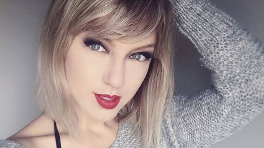 April Gloria als Taylor Swift im grauen Pullover