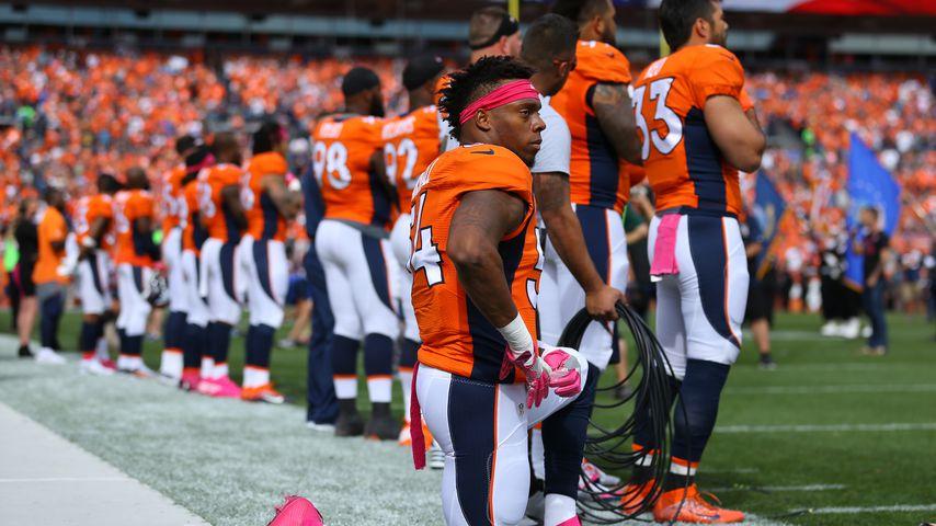 Footballspieler der Denver Broncos auf den Knien