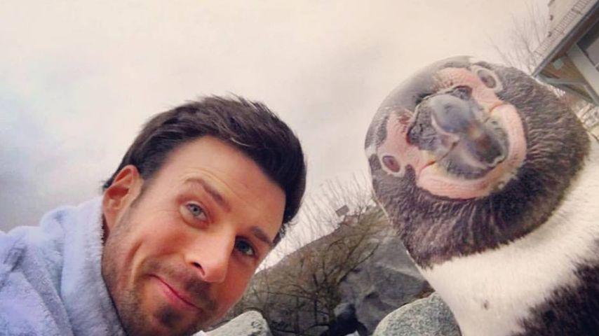 Leonard Freier posiert mit einem Pinguin