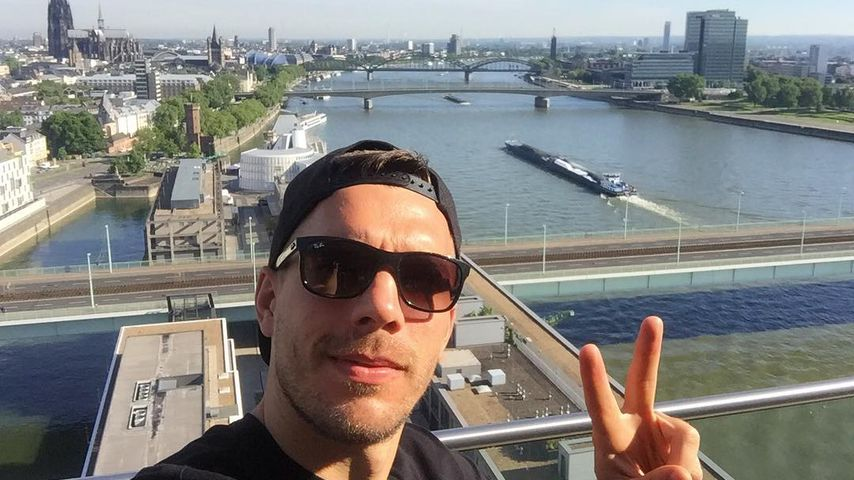 Lukas Podolski vor der Kölner Skyline