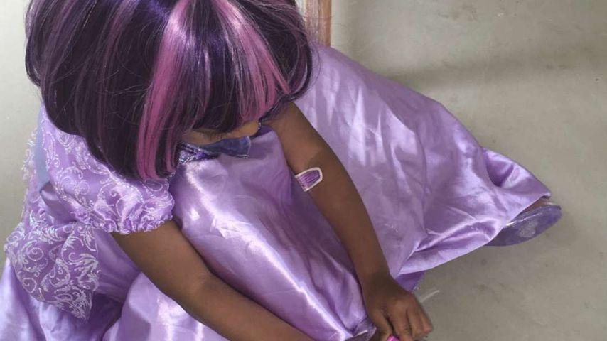 North West spielt und trägt eine lila-farbige Perücke