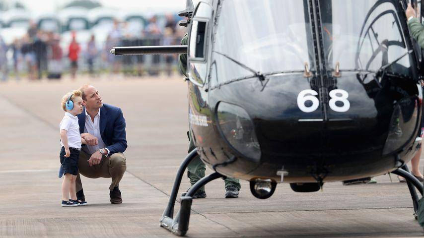Prinz William hockt mit seinem Sohn Prinz George vor einem Hubschrauber