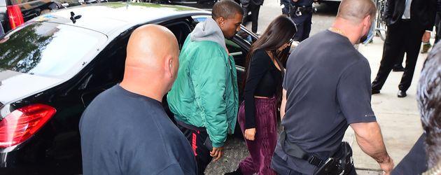 Kim Kardashian und Kanye West, umringt von Bodyguards, in New York